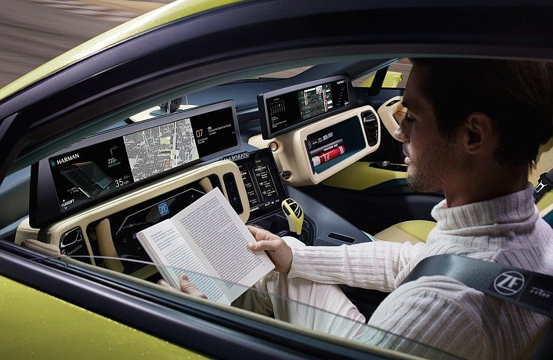Rinspeed Σtos 啟動自動駕駛模式後,方向盤會收納起來,駕駛者可放開雙手做其他事情,像是上圖中人便手執書本閱讀,好不寫意。