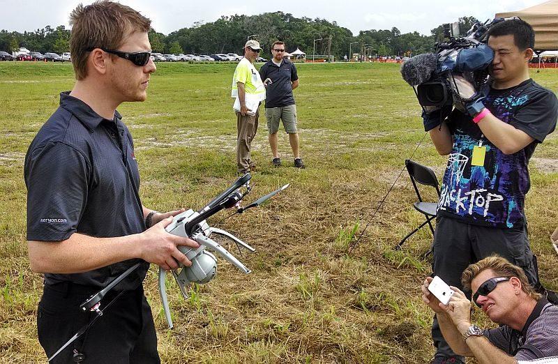 無人機科技公司 Aeryon Labs 的北美銷售總監 Cameron Waite (圖左)向傳媒展示 SkyRanger 無人機。從圖中可見,SkyRanger 飛行器的大小跟一般消費級空拍機相若。