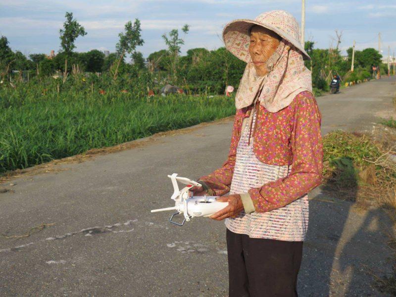 農婦裝扮的阿嬤手持遙控器,神情輕鬆自若。
