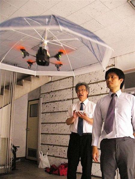 鈴木健治(右)和小林宣夫(左)示範用智慧型手機操控無人機傘起飛。