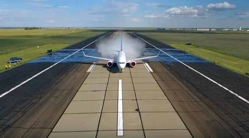 DJI Phantom 4 從正面航拍 Boeing 737 MAX 駛過跑道上水池的情況。