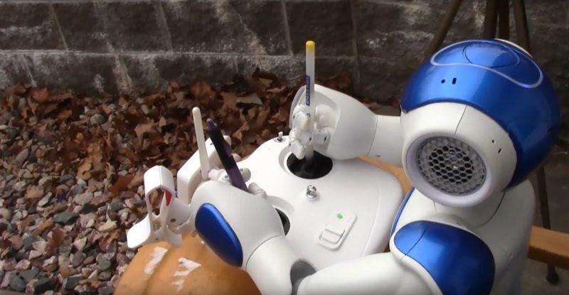 為了讓機器人操控航拍機,還特意用兩支筆加長遙控桿。