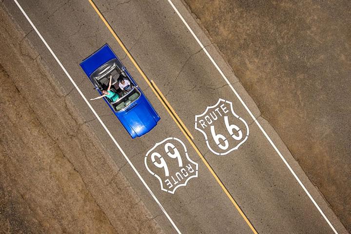 一輛藍色福特野馬敞篷車,在歷史悠久的 66 公路駕駛。(作者:Raf Willems)