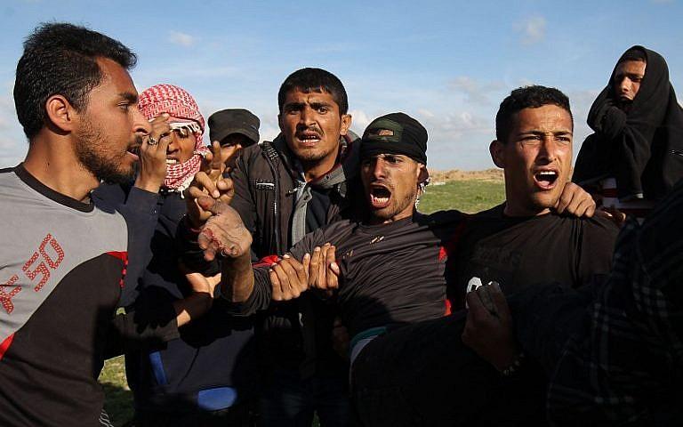南加沙地帶 Khan Yunis 市在 3 月 16 日爆發示威。多名巴勒斯坦男子將受傷示威者抬離現場。