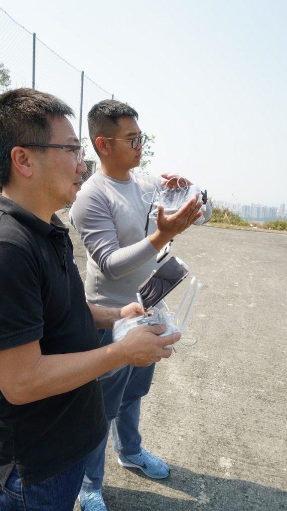 兩名飛手同共關注飛行與拍攝情況。